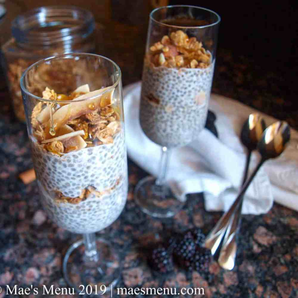 Vegan chia seed pudding parfaits in 2 champagne flutes. Blackberries and two tall spoons sit next to the flutes. A white dish towel and container of granola sit in the background.
