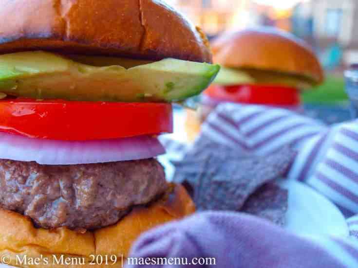 Two juicy hamburgers on white plates separated by a purple striped dish towel.