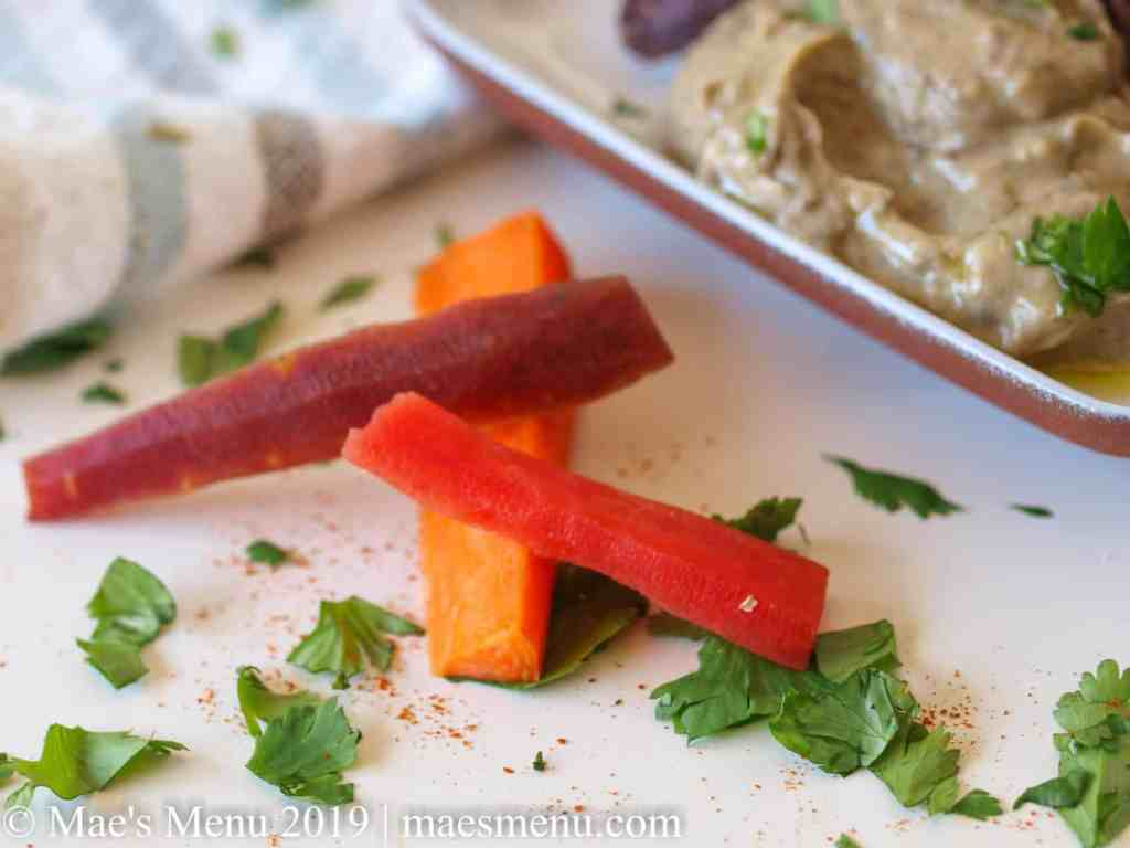 Orange, purple, and red carrots, cilantro, and red pepper next to a dish of creamy avocado black bean dip.