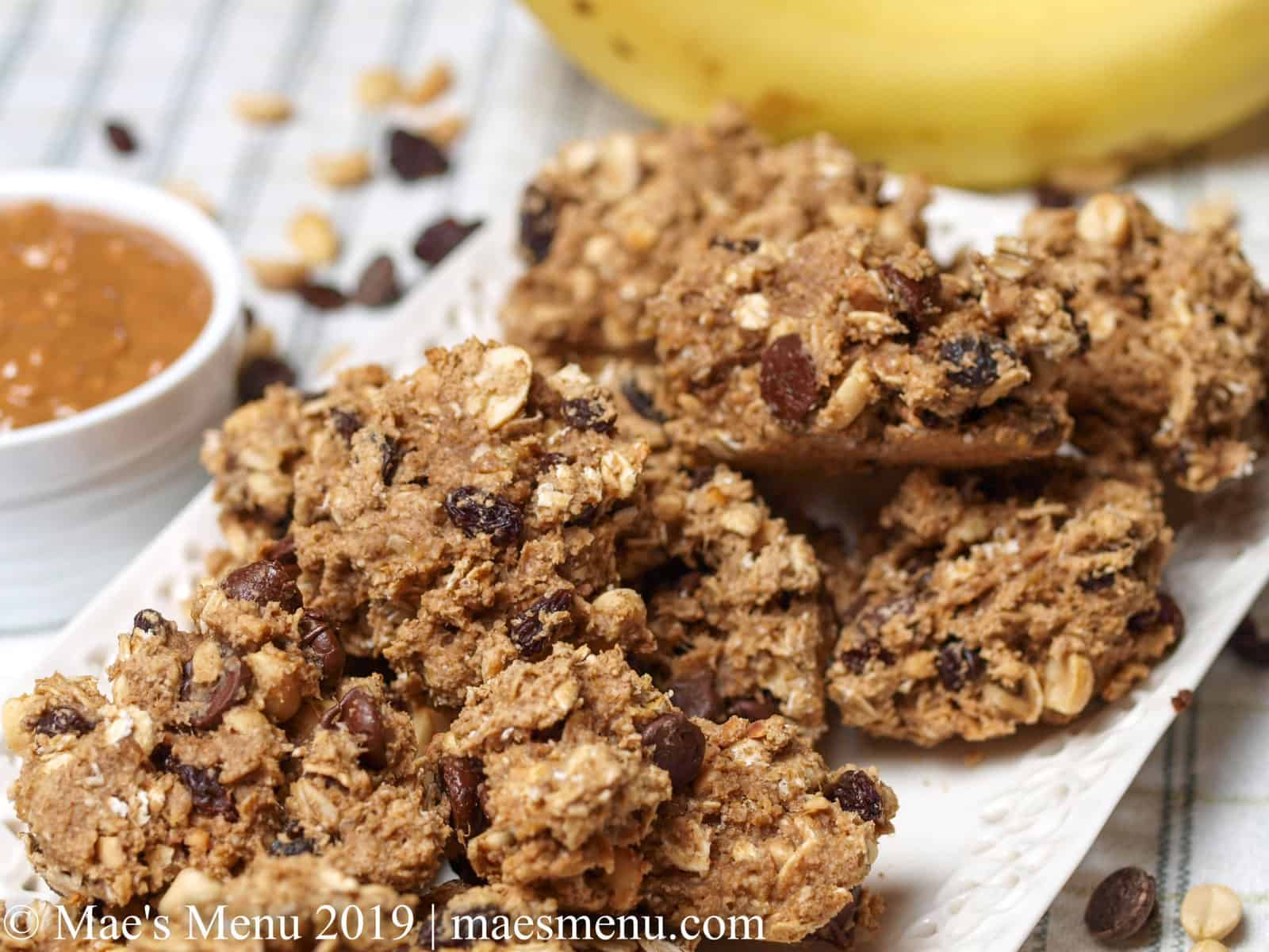 Plate of protein breakfast cookies next to a crock of peanut butter, bananas, peanuts, raisins, and chocolate chips.