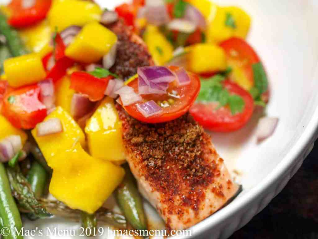 Spicy baked salmon with mango salsa and blistered green beans in a white bowl.