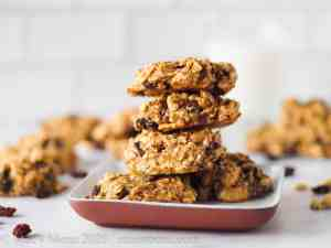 A stack of protein breakfast cookies in front of cookies and a glass of milk