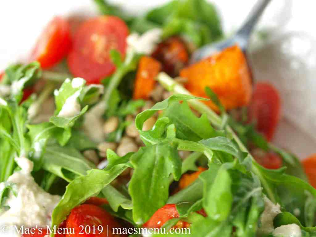 Up close of arugula and vegetables of this healthy lentil and sweet potato bowl.
