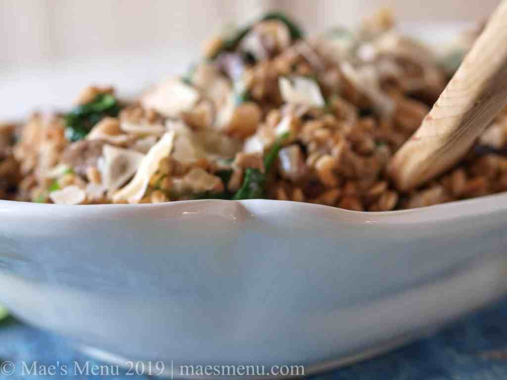 Large bowl of mushroom farro risotto with a wooden serving spoon.