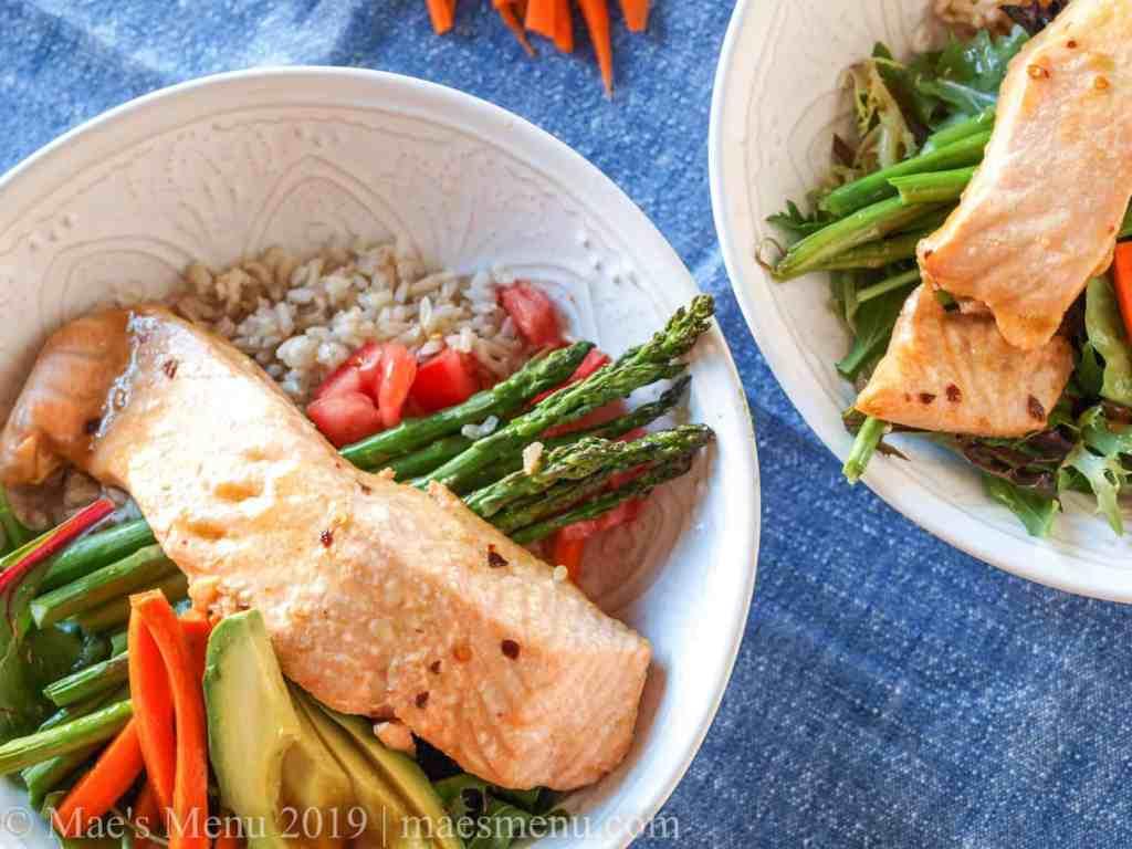 Two salmon protein bowls with orange sesame vinaigrette.