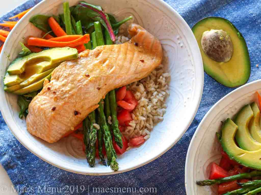 Two power salmon bowls on a blue dish cloth next to an avocado.