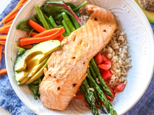 Salmon power protein bowl on a blue dish towel.