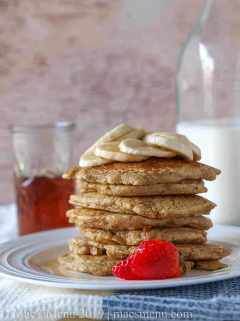 A stack of pancakes in front of a jar of maple syrup and milk
