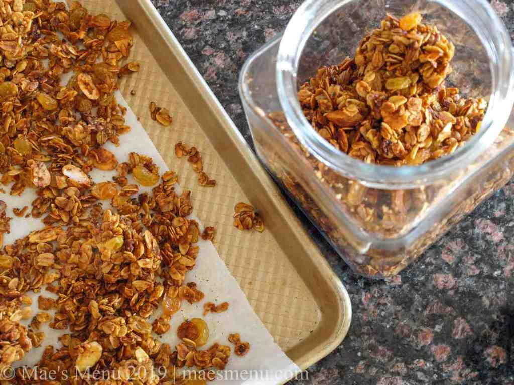 Crunchy turmeric granola on a baking sheet and in a glass canister.