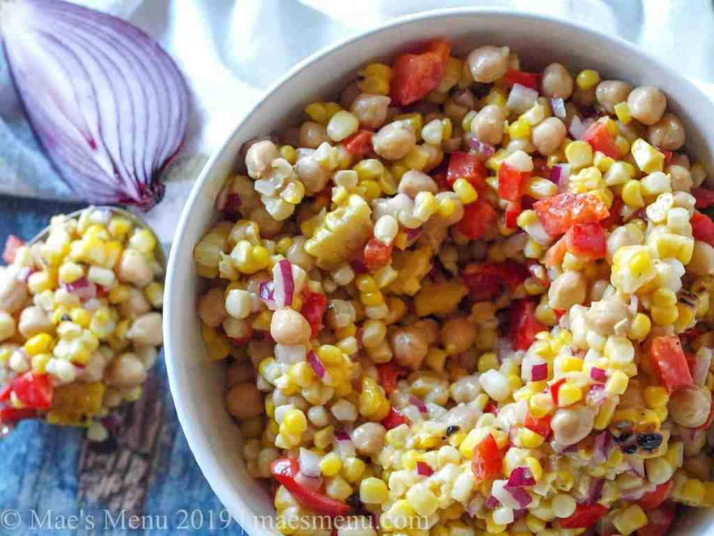 Large white bowl of Chickpea & Grilled Corn Salad with Roasted Garlic Vinaigrette