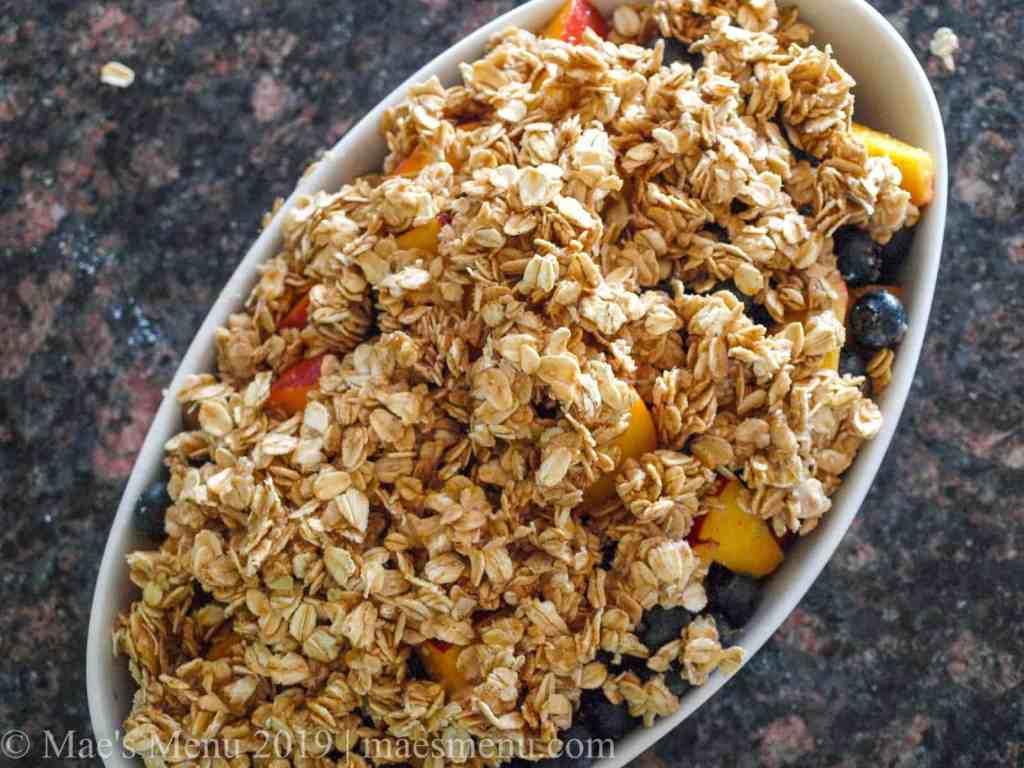 White baking dish of Healthy Blueberry & Peach Crisp before baking.