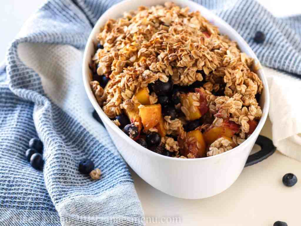 Healthy blueberry peach crumble in a white baking dish with a few scoops taken out.