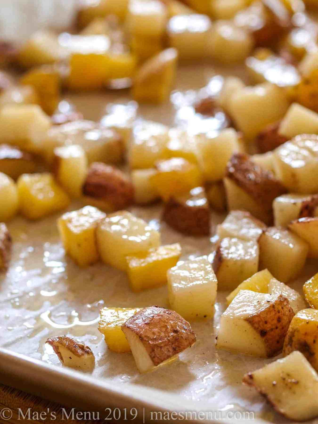 A large sheet pan of roasted diced hash browns.