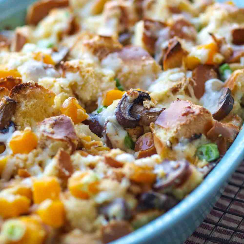 A large pan of savory bread pudding with butternut squash and mushrooms.