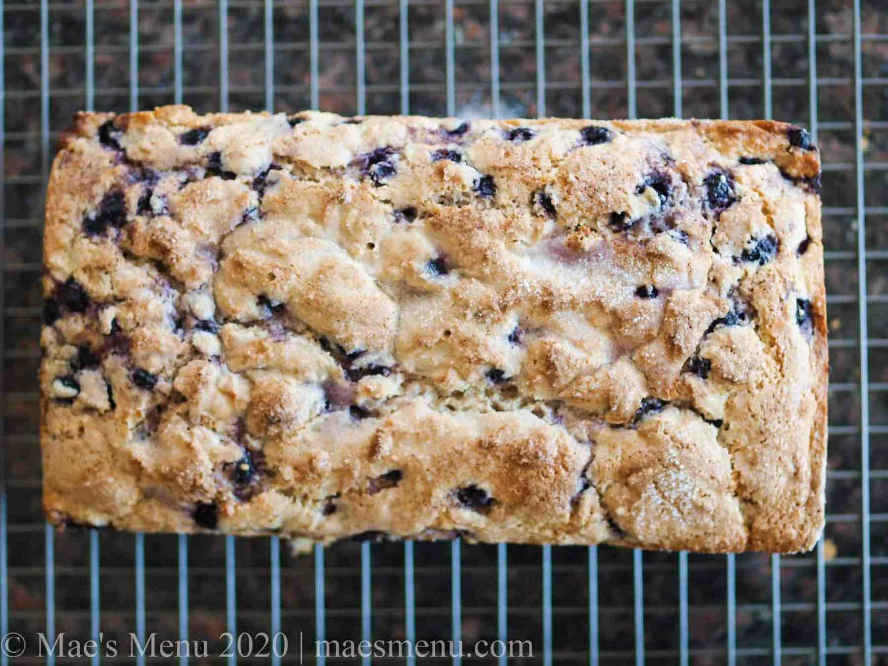 a loaf of lemon blueberry bread on a cooling rack.