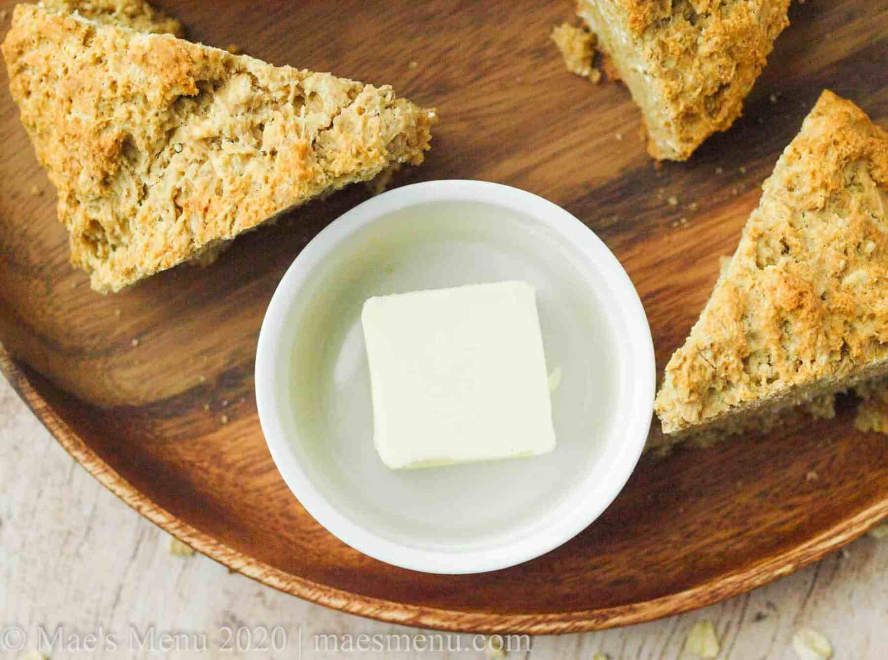 Pieces of oatmeal quick bread next to a crock of butter.