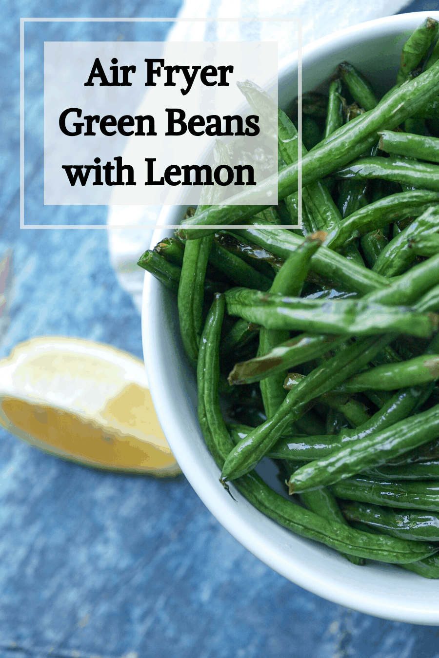 A pinterest pin for air fryer green beans -- a large white bowl of air fried green beans on a wooden board.