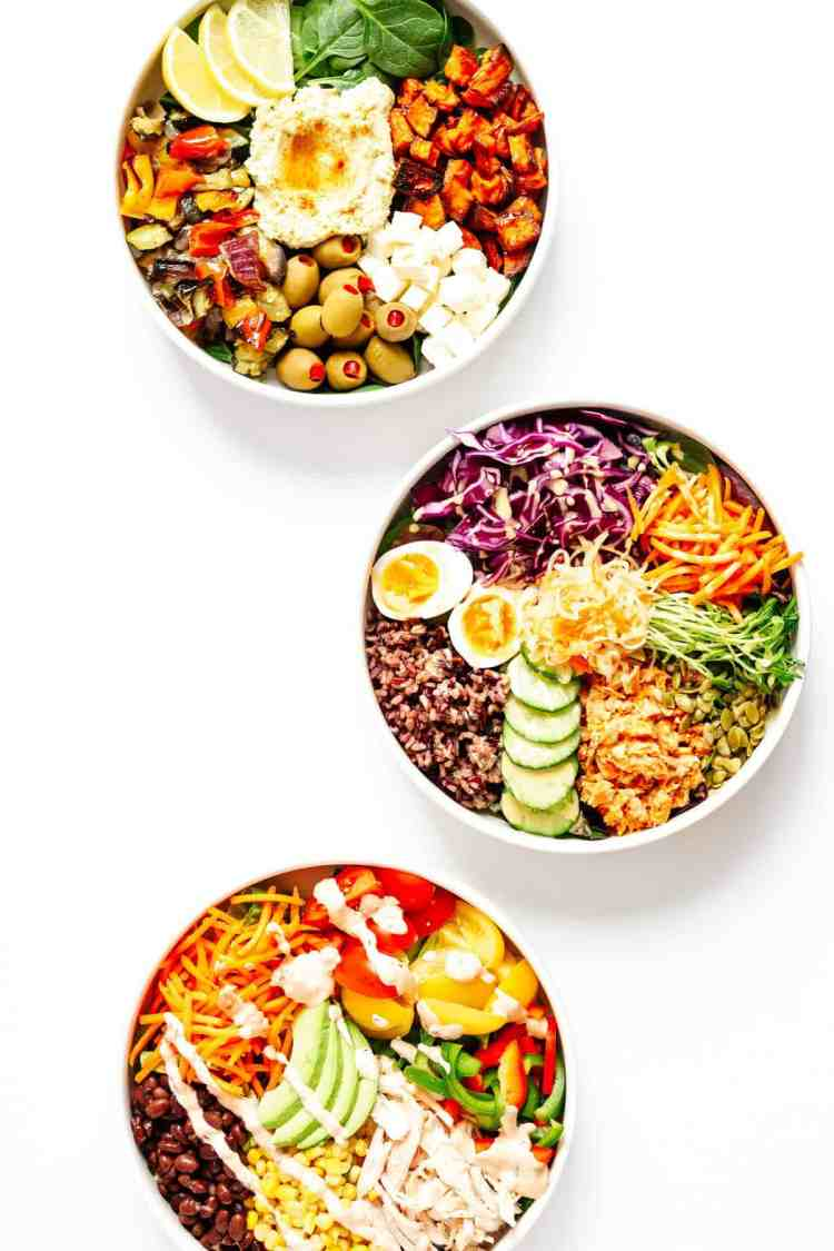 Three white bowls of nourish bowls with all different veggies, cheeses, and different ingredients in them.