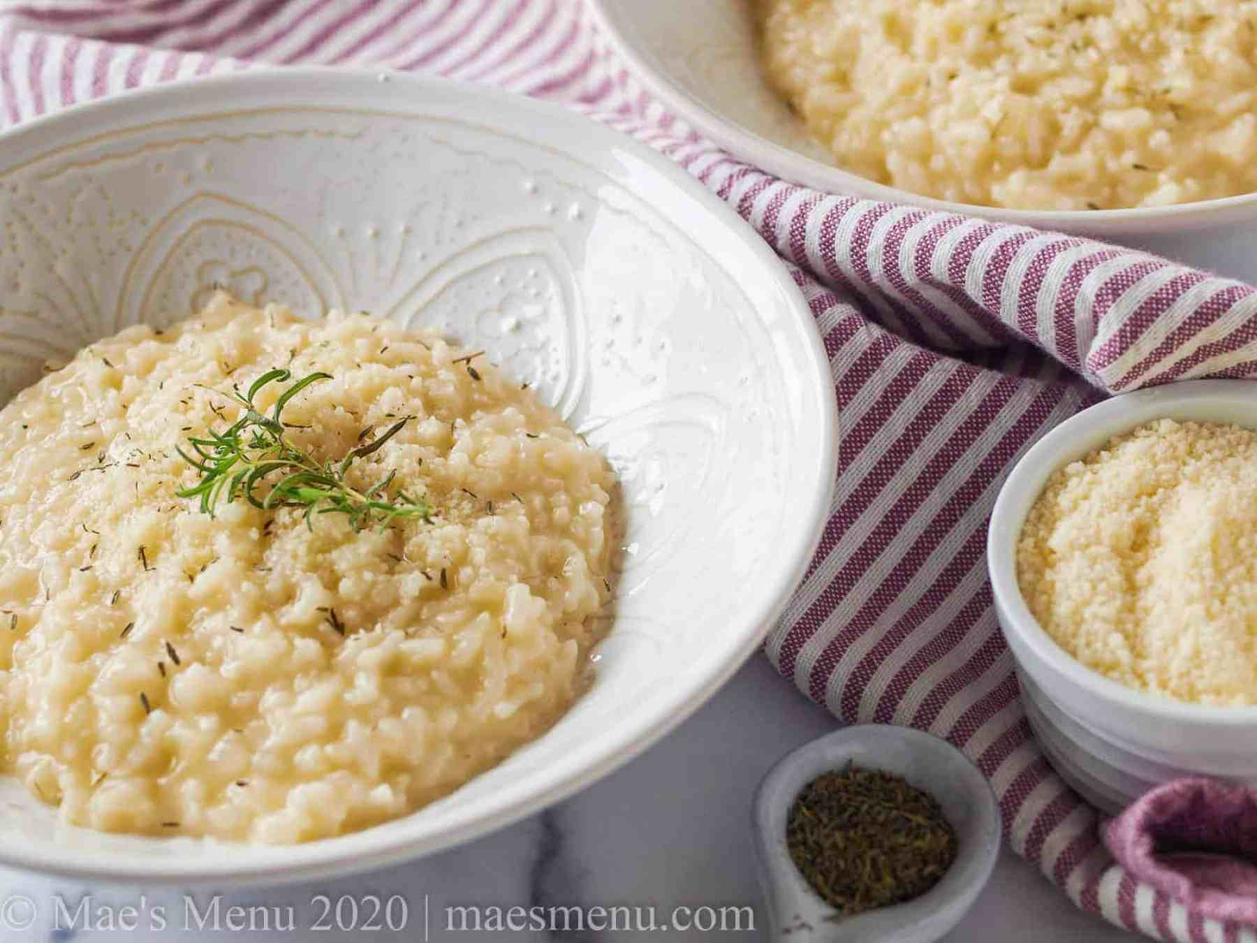 Two white bowls of risotto next to a cup of parmesan cheese and a spoonful of herbs