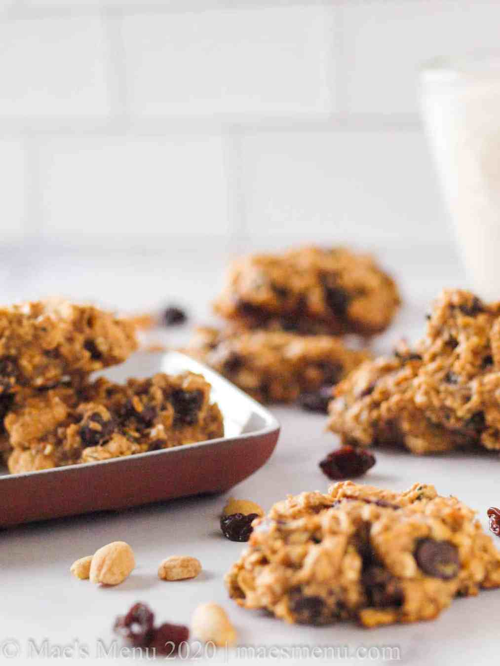 Oatmeal breakfast cookies on a table next to a small plate of cookies, raisins, and peanuts.