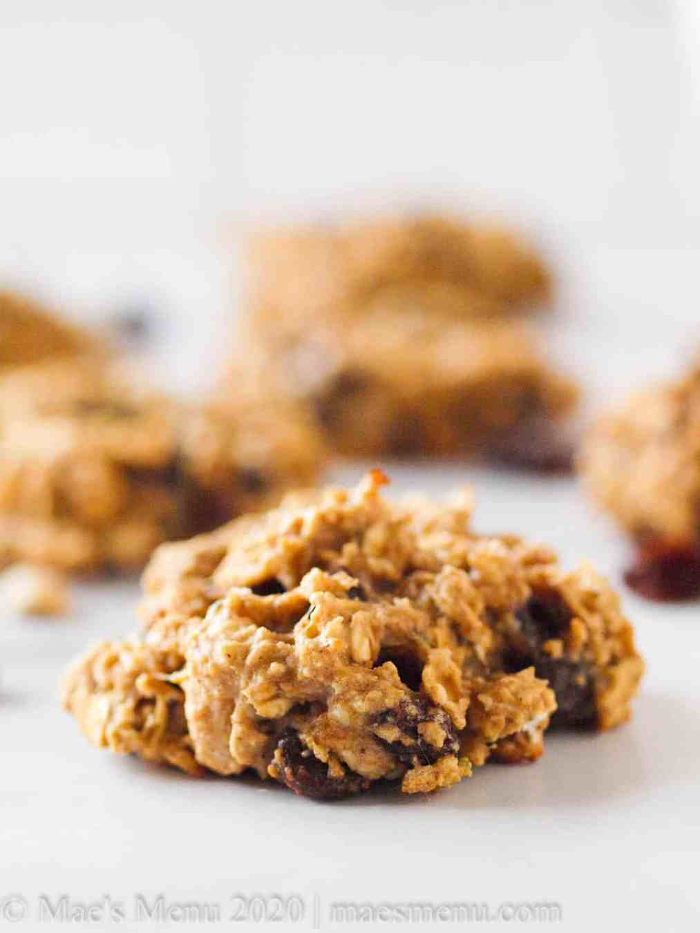 an upclose picgture of an oatmeal protein cookie with other oat protein cookies in the background