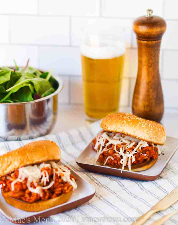Two small plates of sloppy joes on a checkered napkin in front of a bowl of salad, a glass of beer, and a pepper grinder.