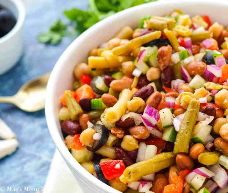 Up-close shot of bowl of 5 bean salad. A spoon, herbs, and the side of a dish of olive sits in the background