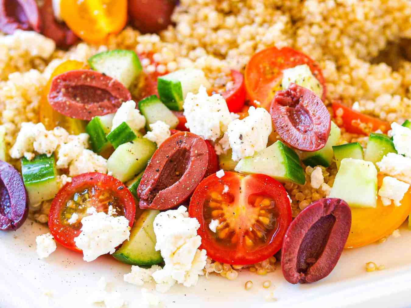 An upclose shot of the olives, tomatoes, cucumbers, sweet peppers, and feta over quinoa