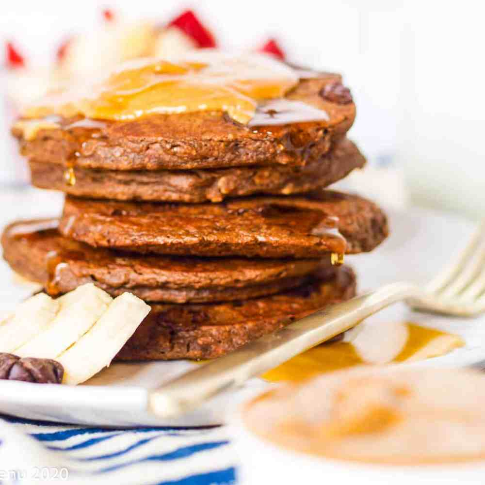 A stack of double chocolate chip banana pancakes with peanut butter and maple syrup on top. The pancakes sit on a white plate next to a fork.
