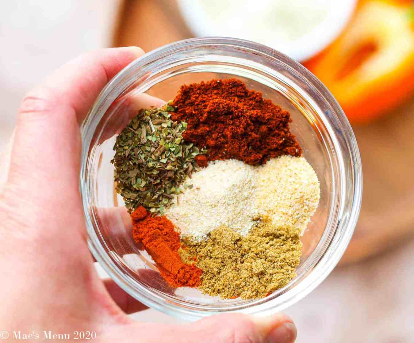 A small clear dish full of taco seasoning spices over a platter of onion and peppers.