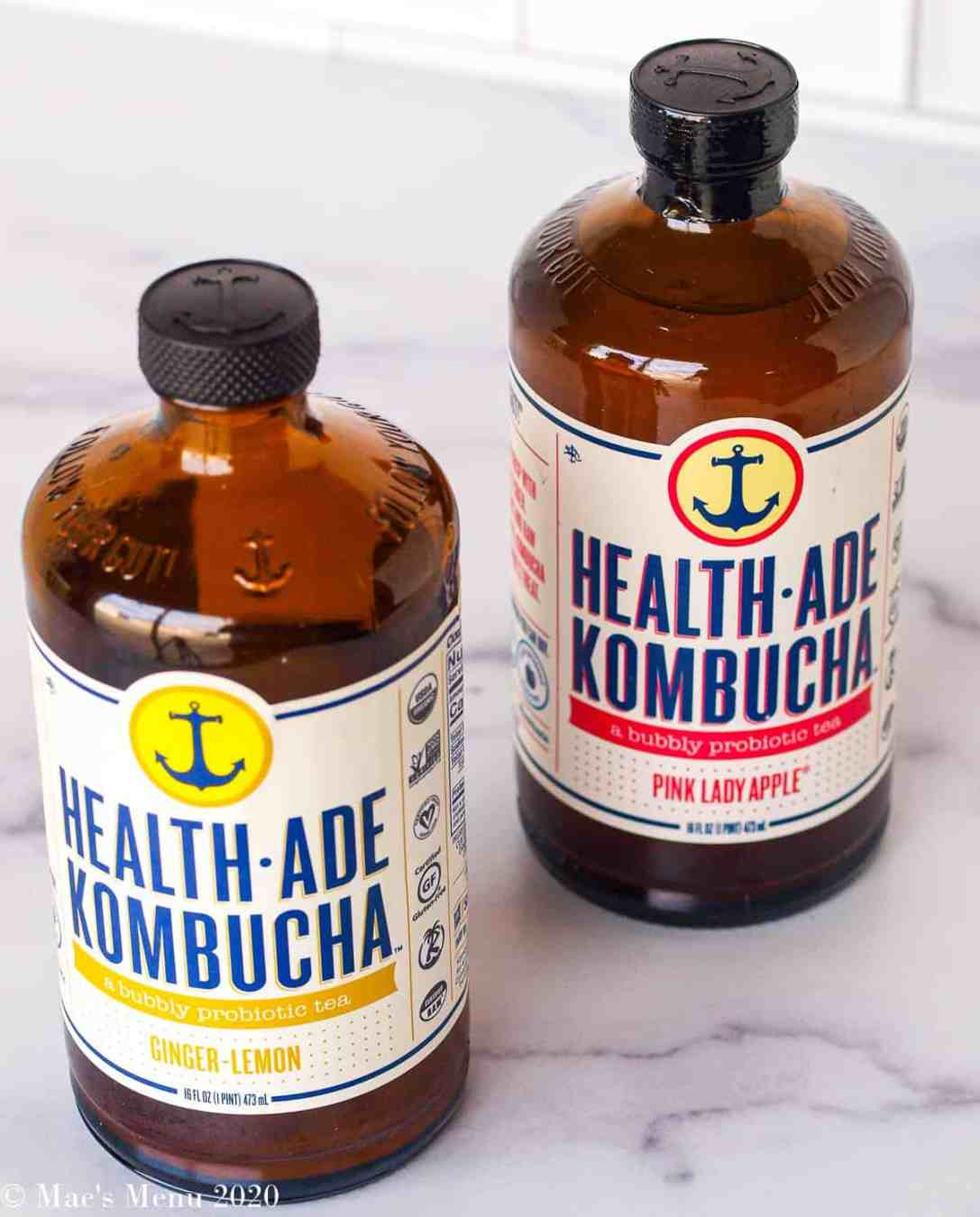An above shot of two bottles of health ade kombucha. One bottle is lemon ginger and the other is pink lady apple.