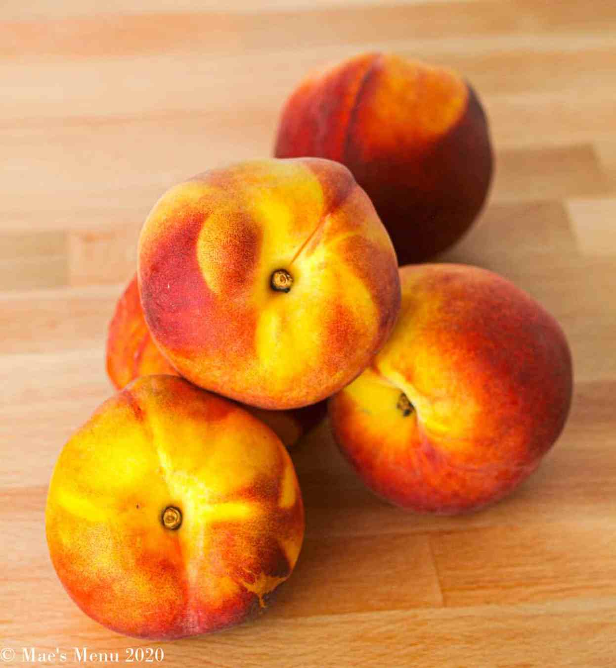 5 peaches sitting on a butcher block counter