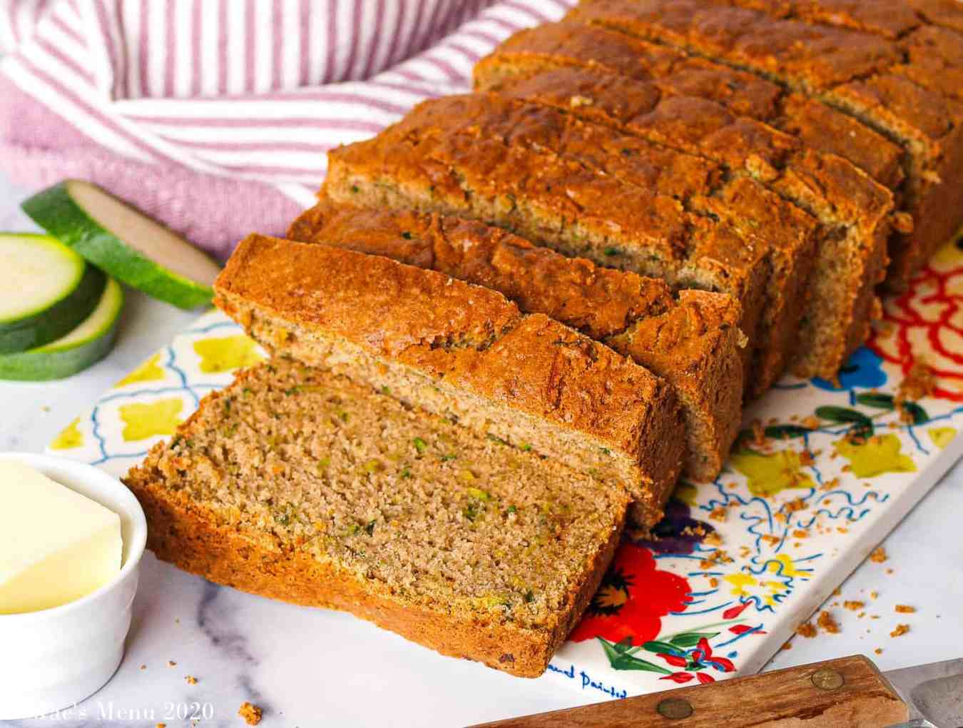 a side shot of a loaf of gluten-free zucchini bread sliced on a flowered platter