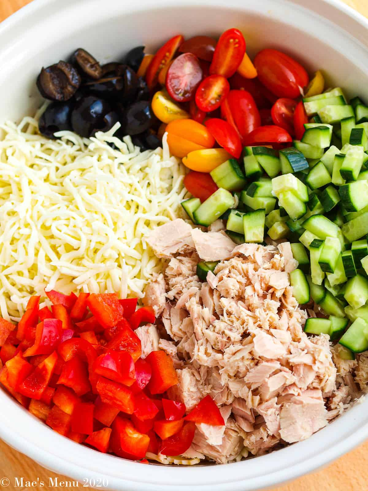 An overhead shot of a bowl of tuna pasta salad before stirring.