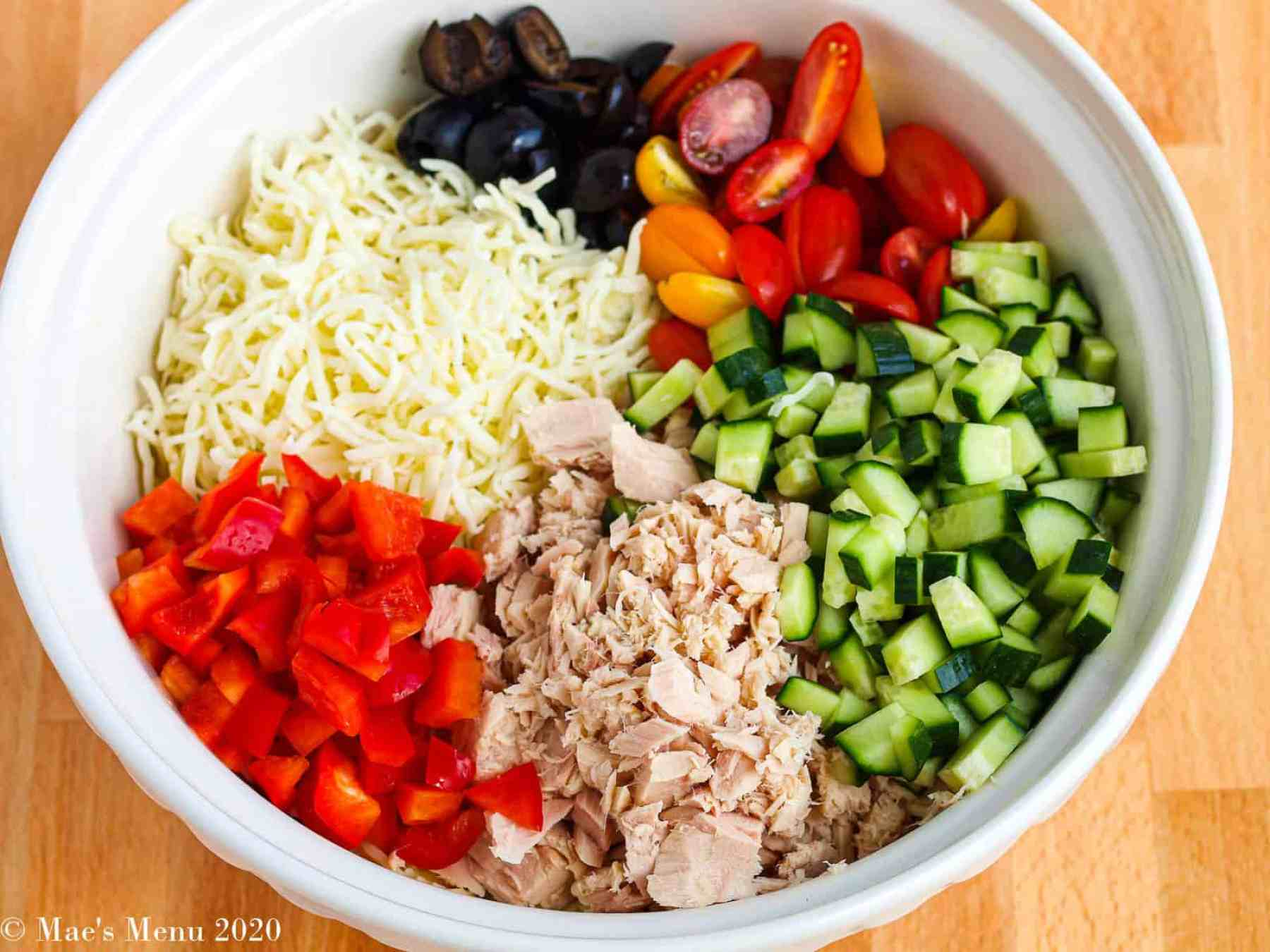 An overhead shot of a bowl full of ingredients before being mixed for the salad.