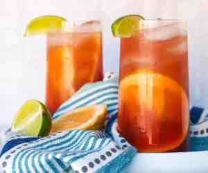 Two large glasses of pomegranate sea breezes sitting on a white platter with a blue striped towel and lime and grapefruit wedges sitting between them