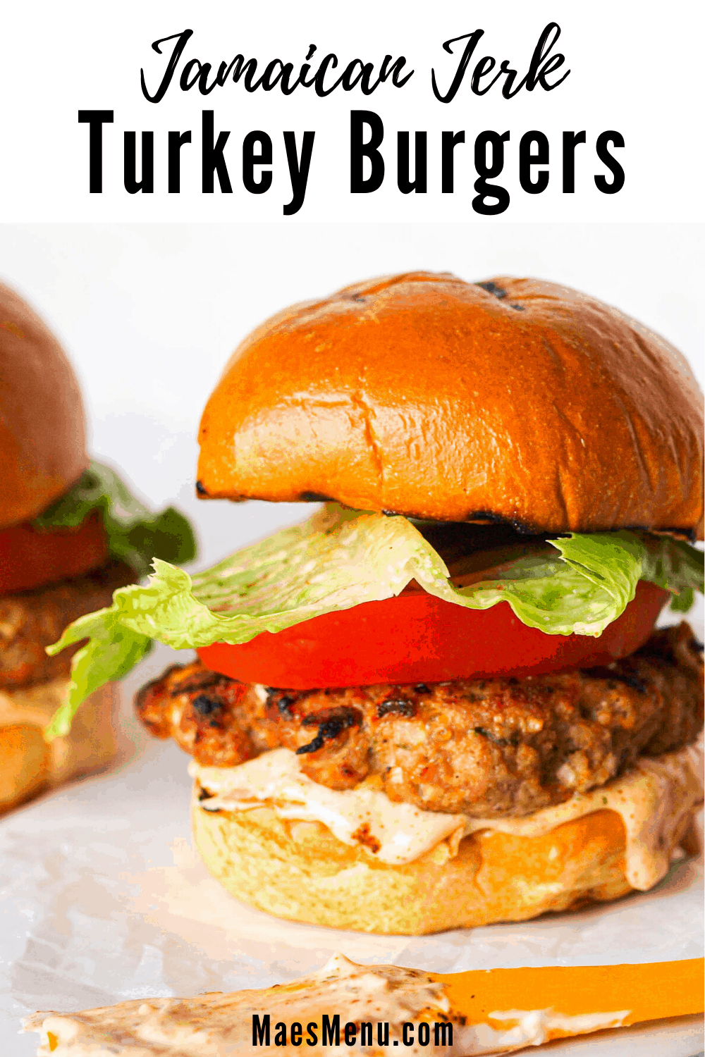 A pinterest pin for Jamaican Jerk Turkey Burgers with an up-close picture of a turkey burger with a spatula in the foreground.