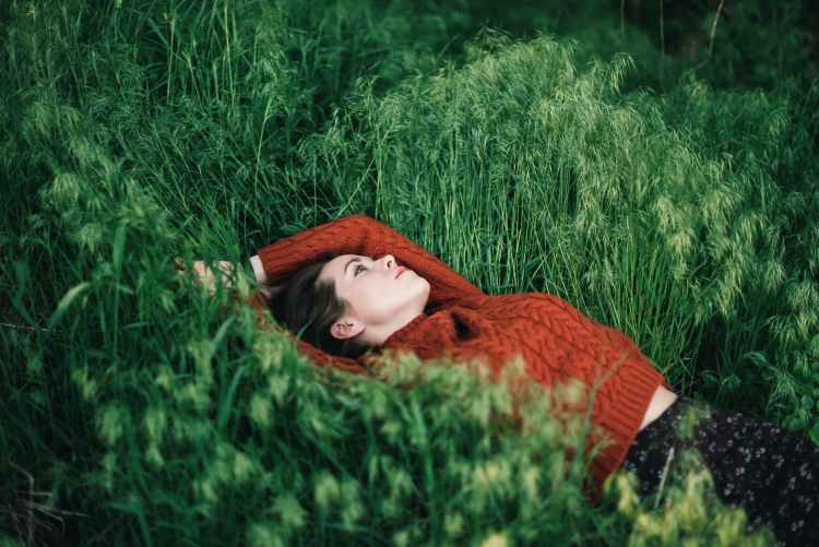 thoughtful woman lying on grass