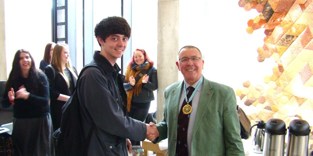 I Fallon receiving his graduate award from MAFA president, Gerry Halpin MBE PMAFA