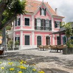 A picture of Zino's palace, a restored 1905 Portuguese building in light pink, seen from the terrace with yellow flower beds, large tree and terrace chairs framing the foreground