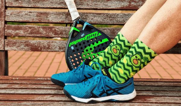 Calcetines de aguacate jugando a pádel, de color verde, con zapatillas azules y pala de fondo
