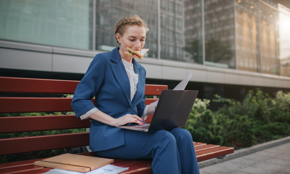 Busy woman is in a hurry, she does not have time, she is going to eat snack outdoors. Worker eating and working with documents on the laptop at the same time. Businesswoman doing multiple tasks. Multitasking business person
