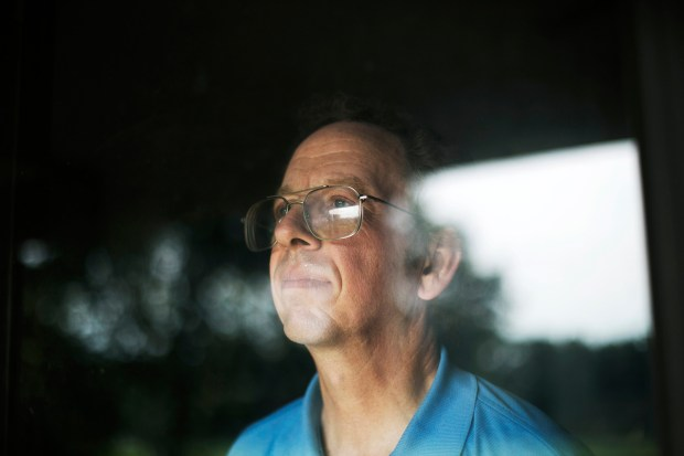 Fowle looks through the front door of his home.