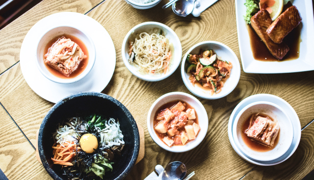 A table with a selection of Korean foods including Kimchi.