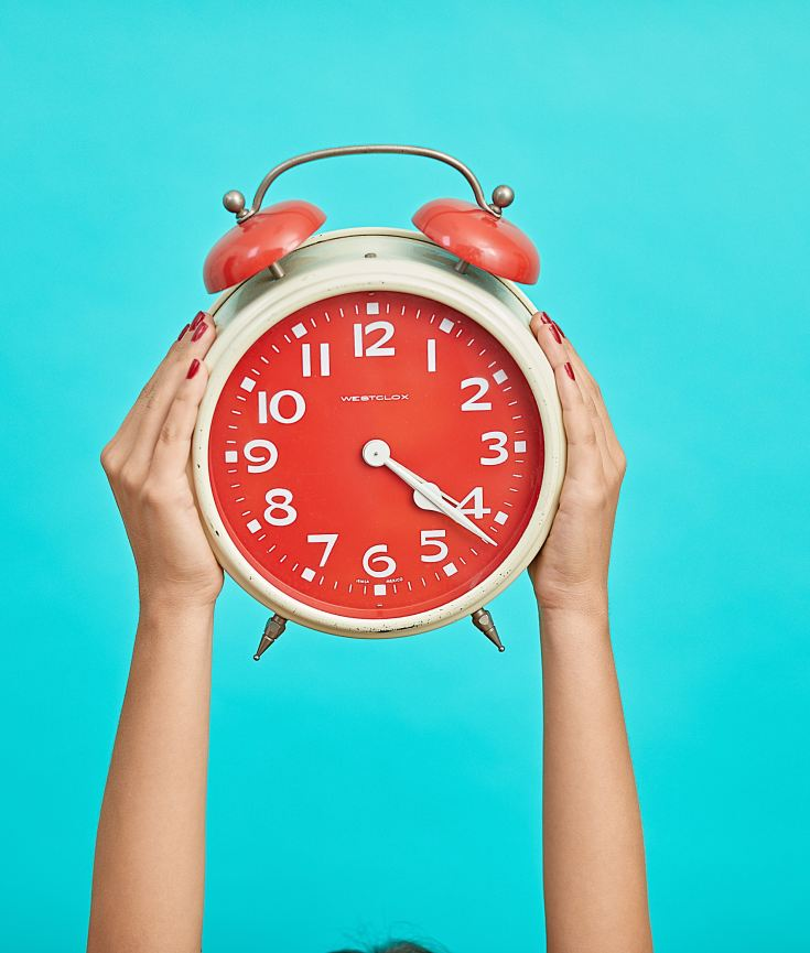 woman holding up a clock to show time expectations with supplements