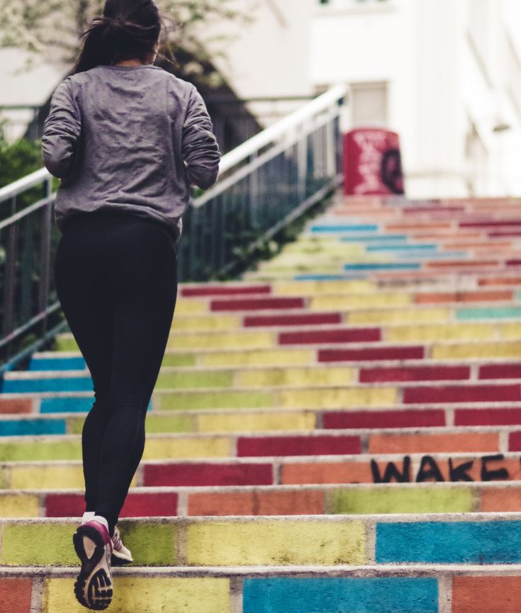 active woman doing physical activity. running up brightly colored stairs
