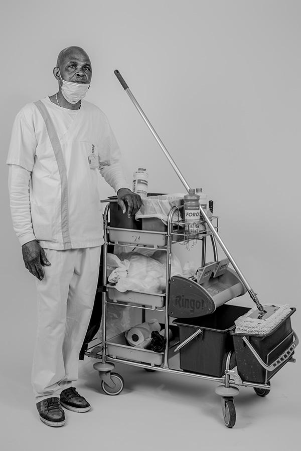 Nosa Aikpitanyi, un addetto alle pulizie in un reparto di emergenza della Uniklinik Bonn, posa per un ritratto. Bonn, Germania. 5 maggio 2020. Aikpitanyi, originario della Nigeria, pulisce il reparto di emergenza da più di dieci anni. © Daniel Etter