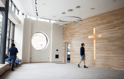 The Harvey Prayer Chapel, not quite completed in this image, faces northeast toward the Pine Grove. Stained glass will fill the circular window. The wall at right is paneled with wood from campus trees felled by storms or age — all a part of students' experience for decades, some older than the college itself. Photo by Steven Herppich