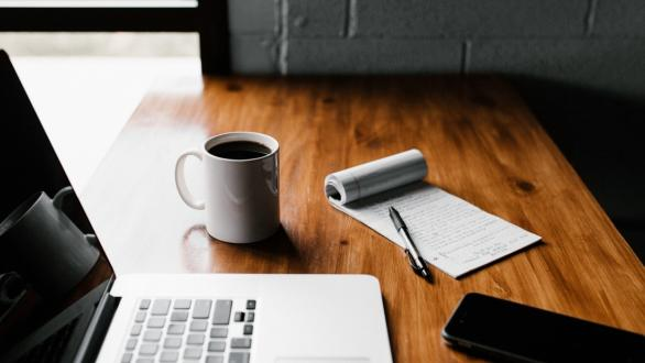 A laptop, cup of coffee, and notepad on a small wooden table
