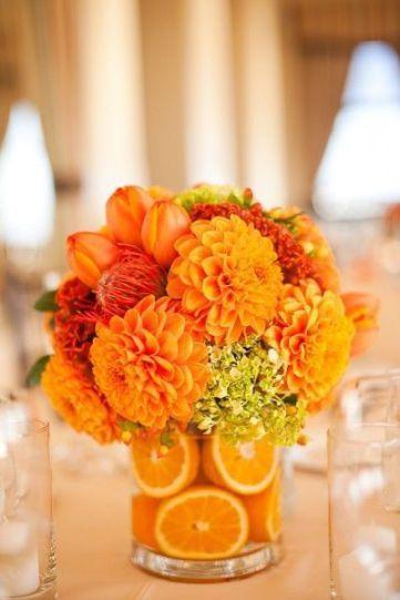 centrotavola estivo con fiori arancioni e fette di arancia